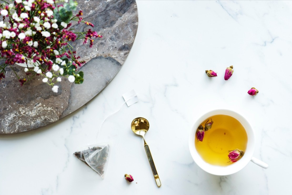 cup of tea, flowers, and spoon on table
