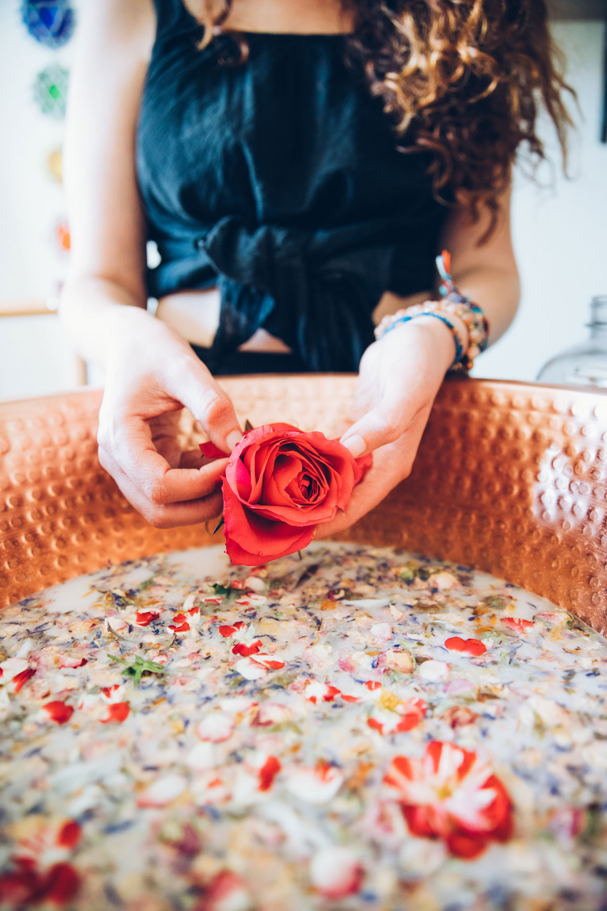 Woman holding a rose over a copper bowl filled with herbs and salts.