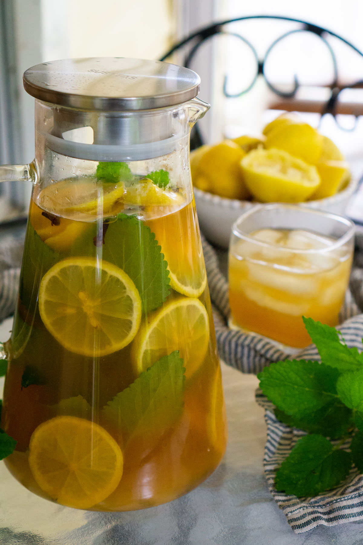 Pitcher of Arnold Palmer iced tea on table with glass and lemons in background