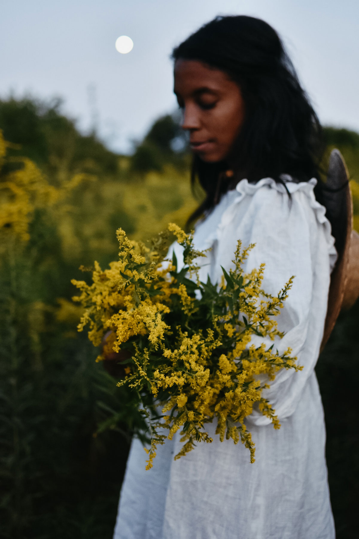 Alyson Morgan holding goldenrod in a field with the moon behind her