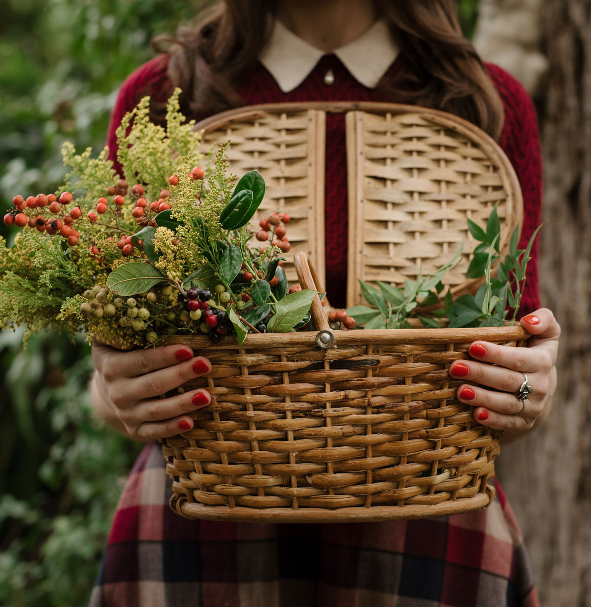 Woman in red sweater holding a foraging basket with goldenrod in it