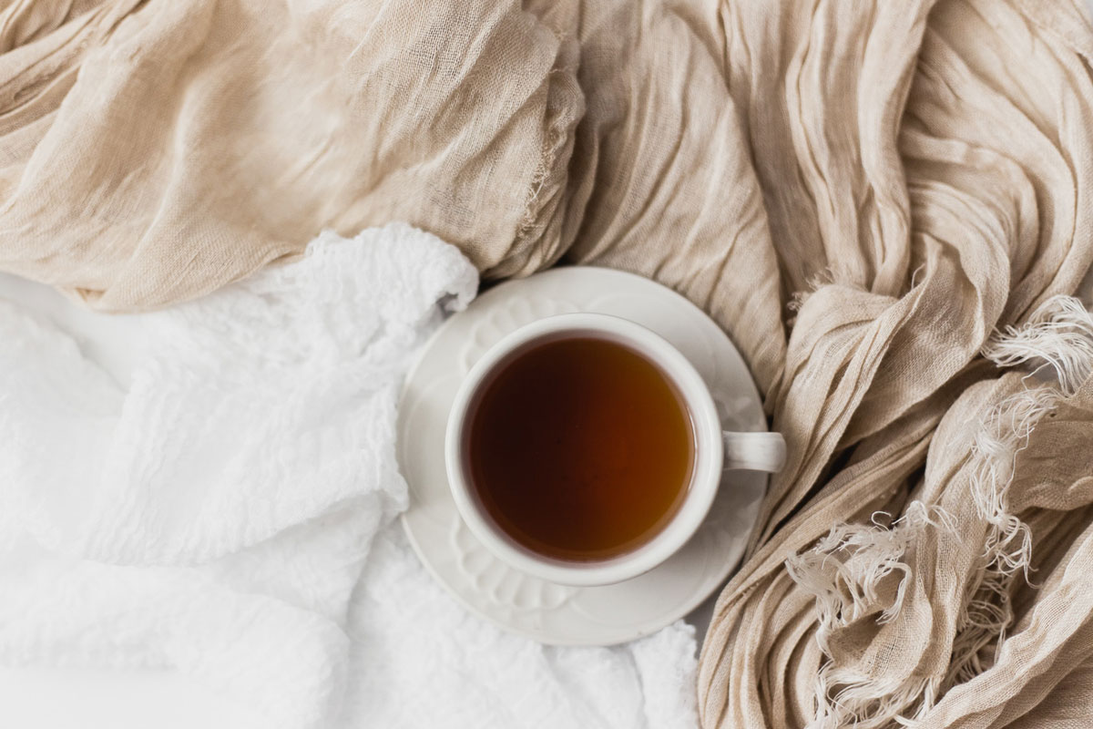 A cup of tea sitting on top of neutral-colored linens