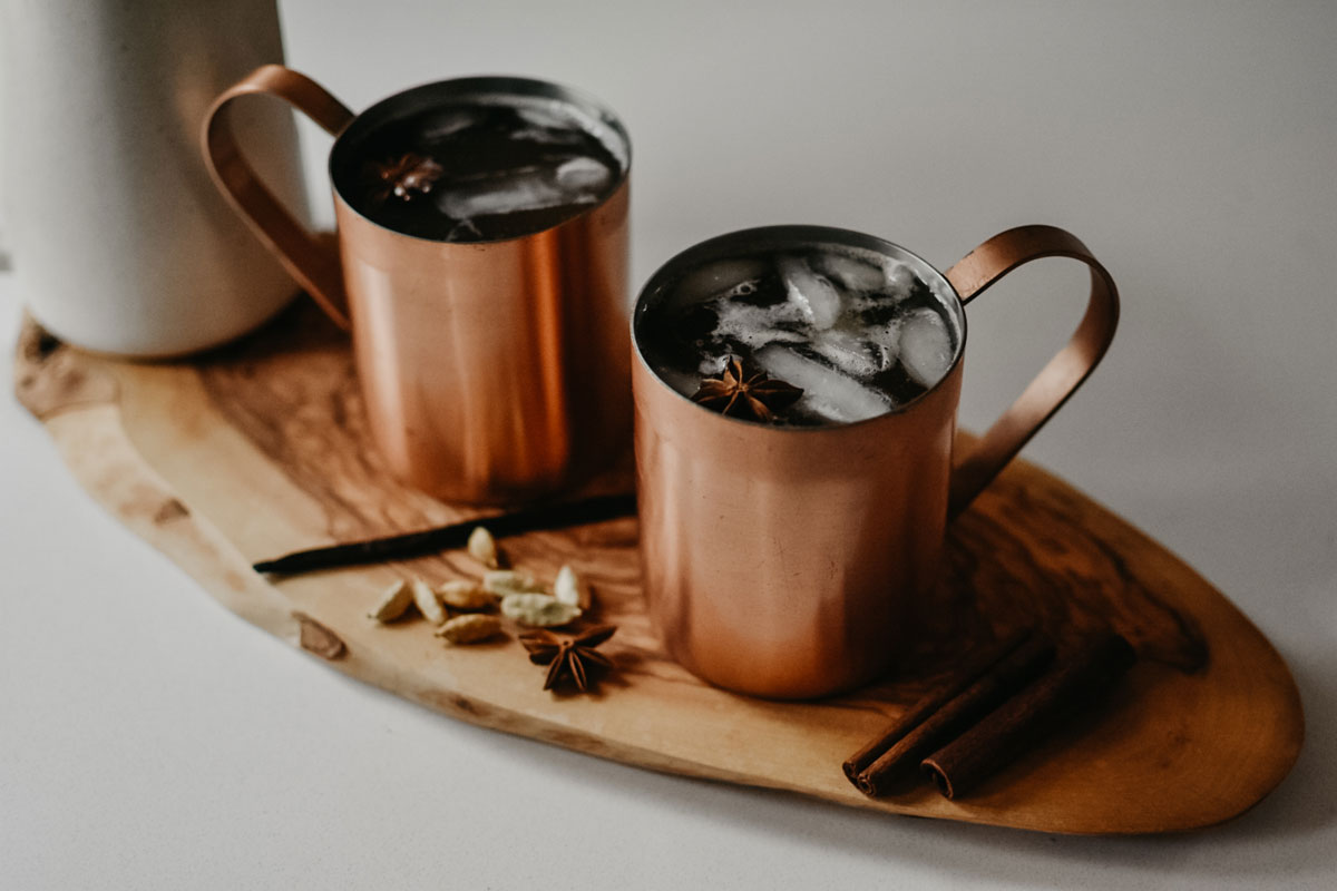 chai-spiced apple cider in copper mugs on a wooden cutting board