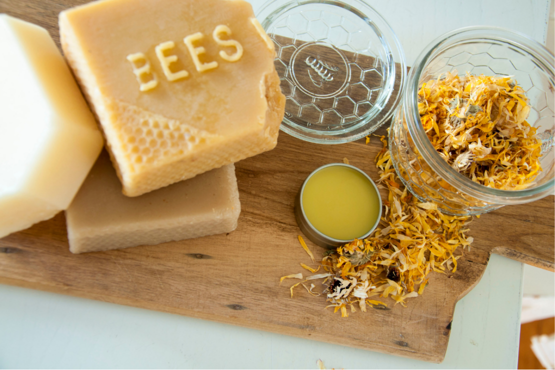 Homemade Nipple Balm with Marshmallow and Calendula | Herbal Academy | bees wax and flowers on table