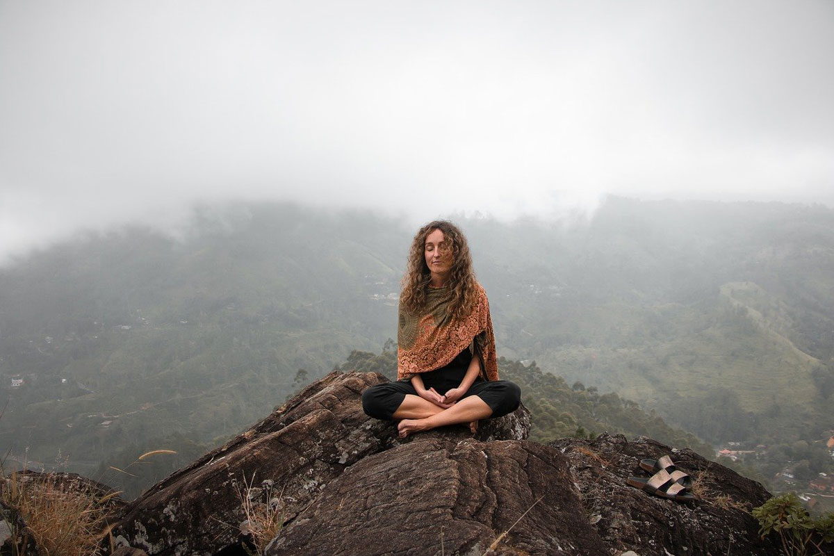 A woman sitting on a mountaintop meditation peacefully