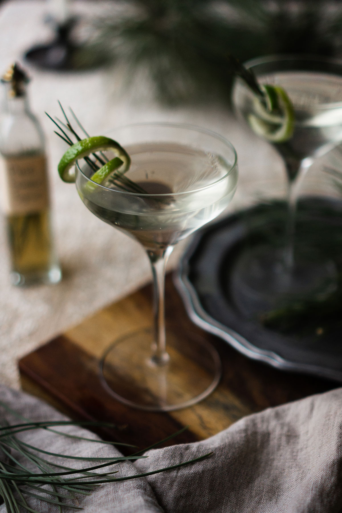 pine needle gimlet on a wooden cutting board