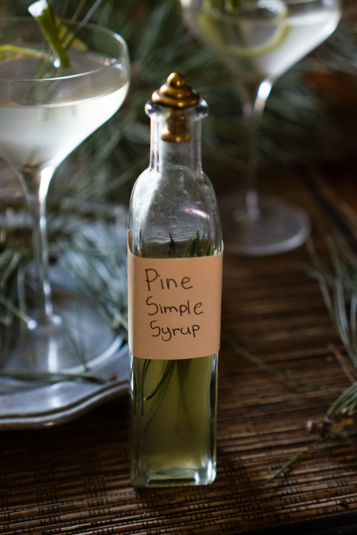 Pine needle simple syrup bottle on a table