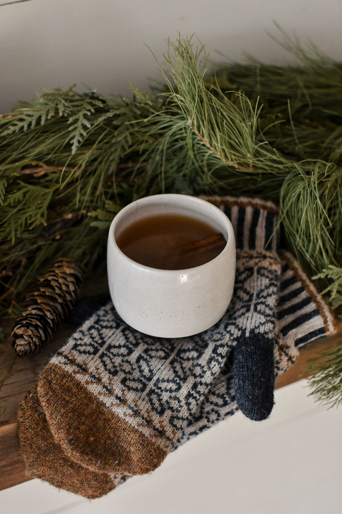 Spiced apple cider in a mug sitting on top of a pair of cozy mittens