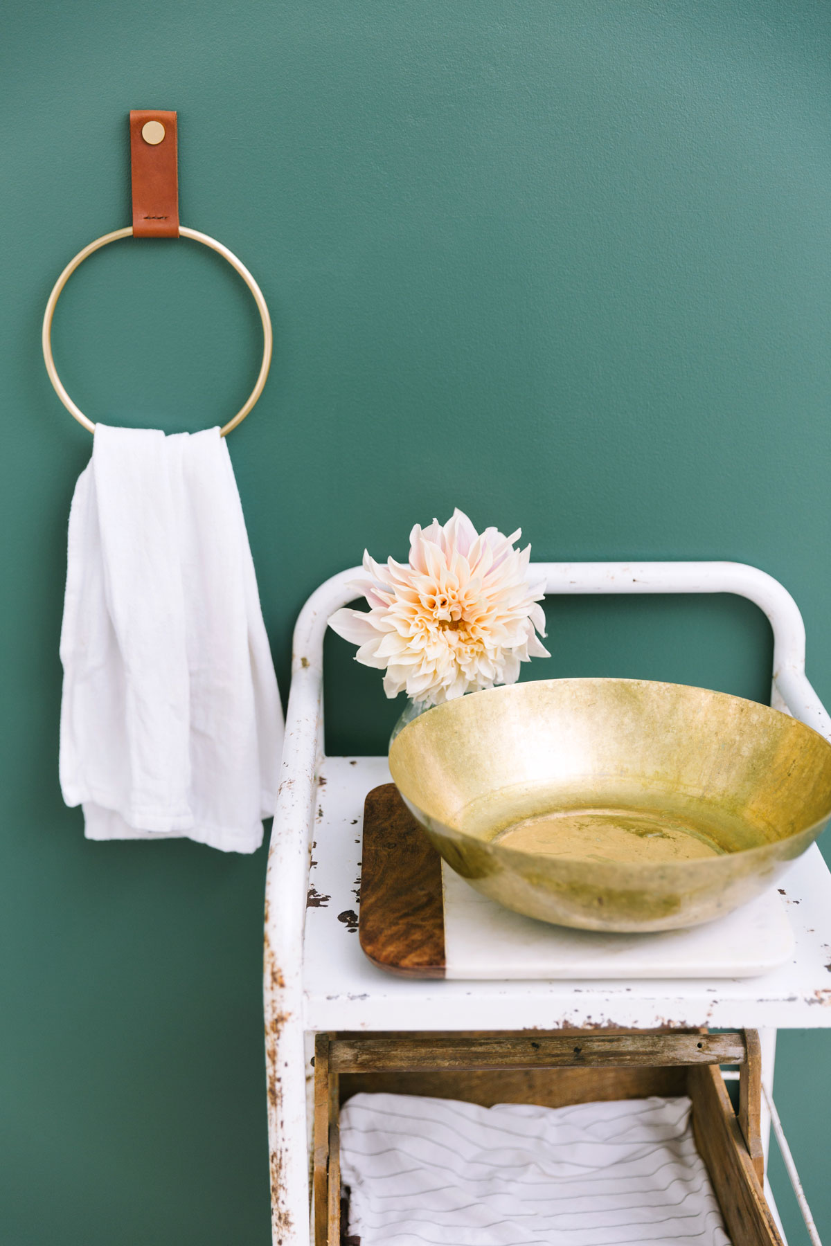 A hanging towel, golden bowl, and white stand ready for a skincare ritual.