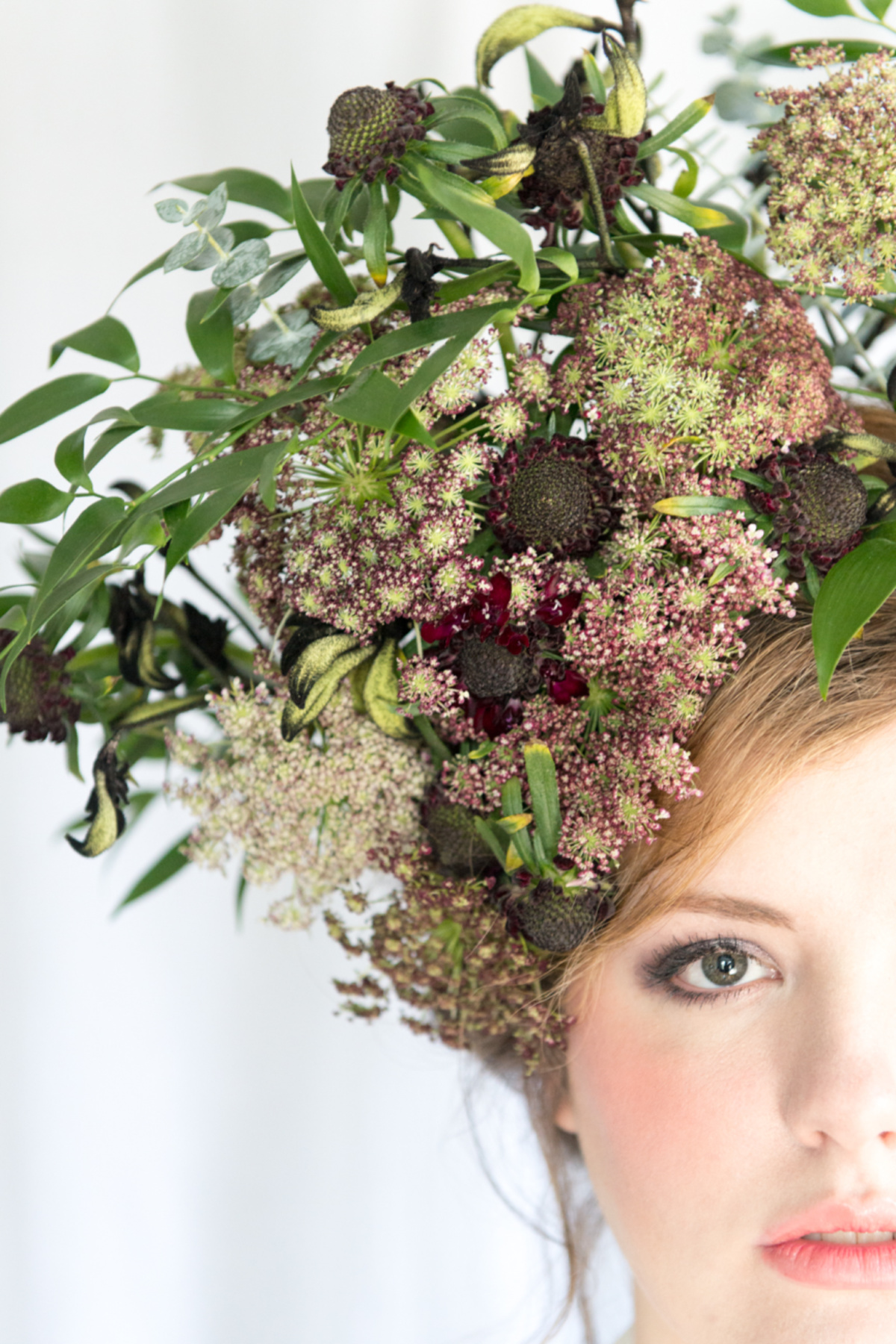 half of a lady's face looking at the camera with flowers in her hair
