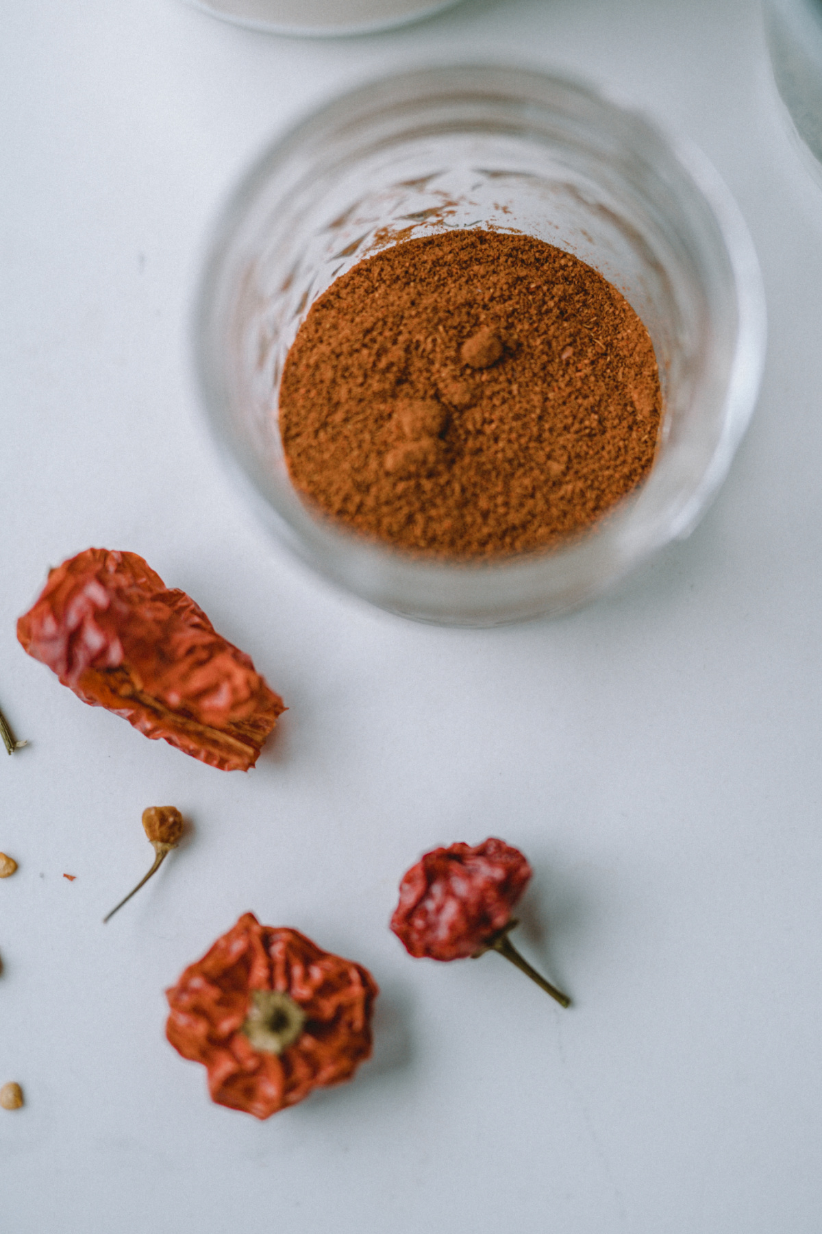 powdered cayenne in a glass bowl with dried cayenne on the table next to it