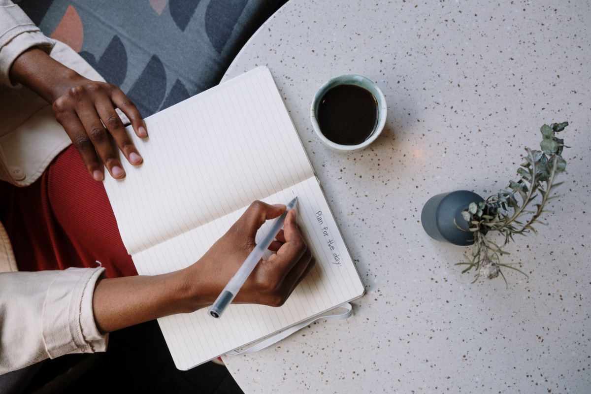 lady writing in a notebook with a cup of coffee and plant next to her