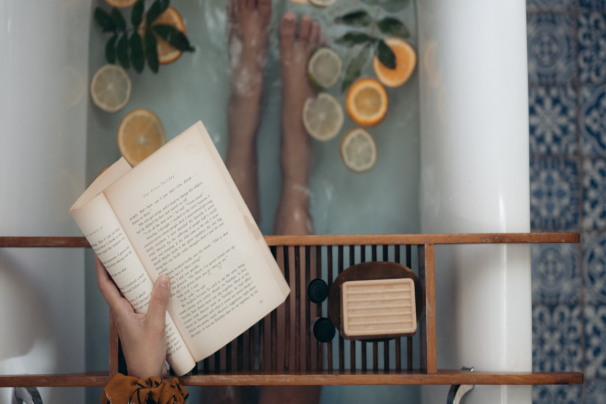 woman reading a book while in the bathtub with floating lemon and orange slices in the water: a relaxing way to boost immunity