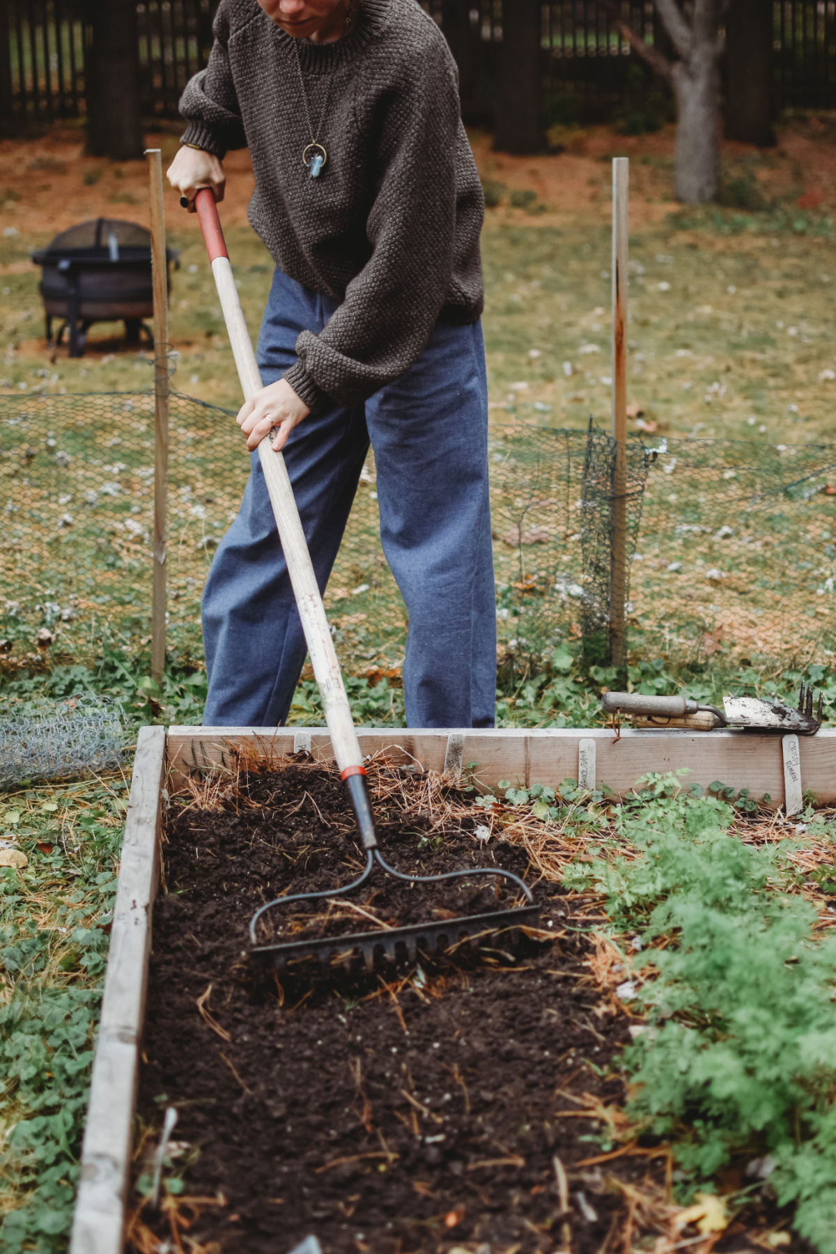 woman digging in the soil with a rake
