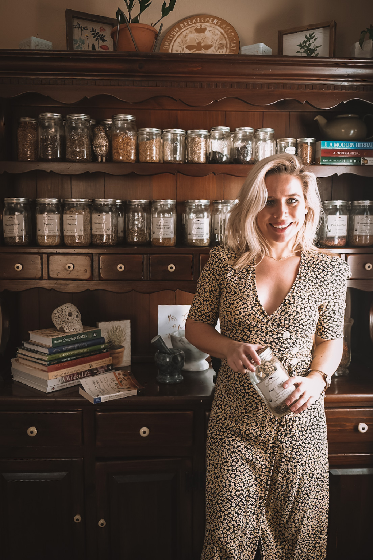 herbalist Caitlin Frazier standing in front of a shelf full of herbs and herbal books