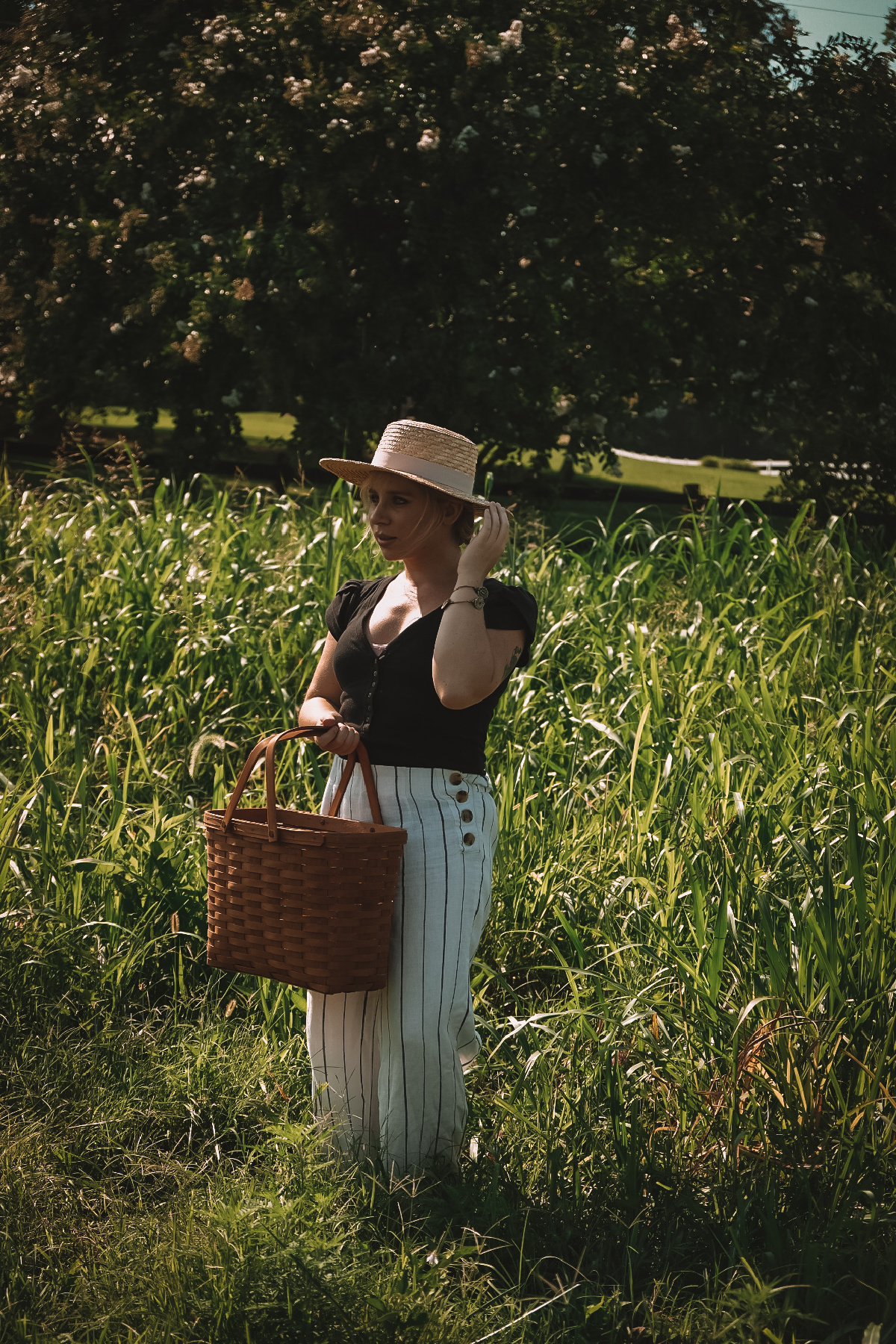 herbalist Caitlin Frazier in a field holding a basket