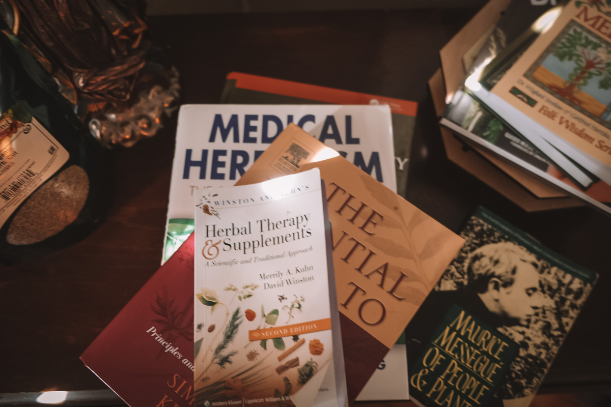 stack of herbal books on a table