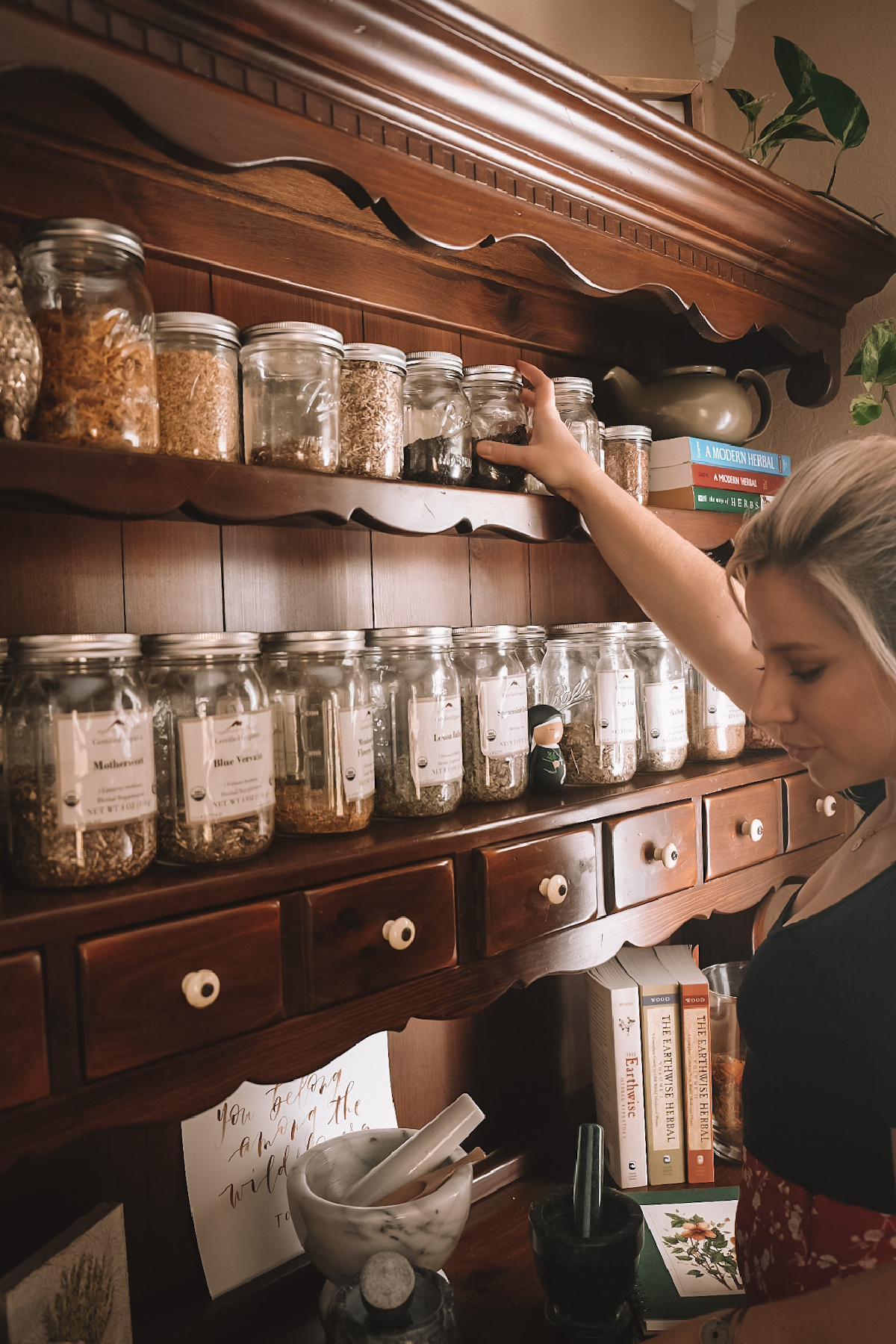 Herbalist Caitlin Frazier reaching for a jar of herbs