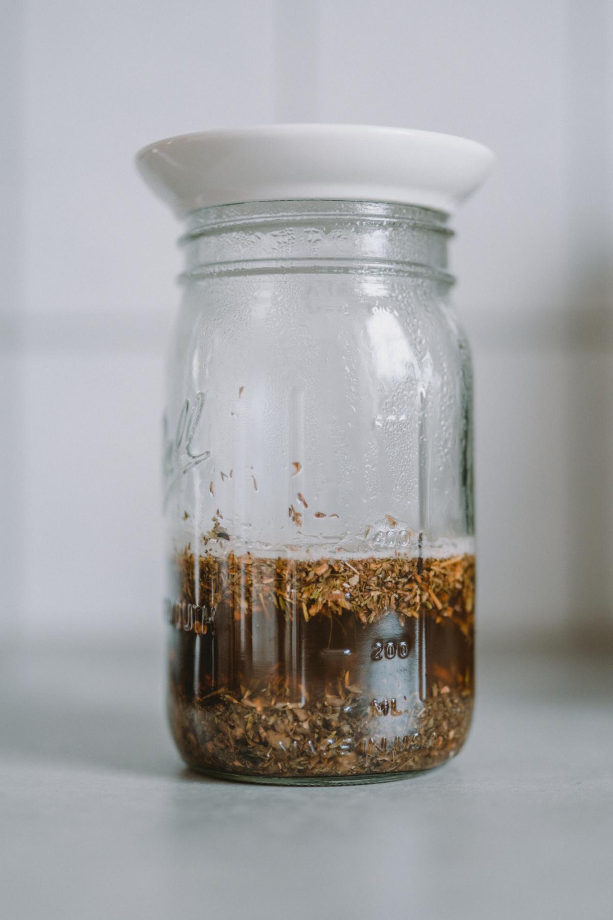 covered jar of infused herbs
