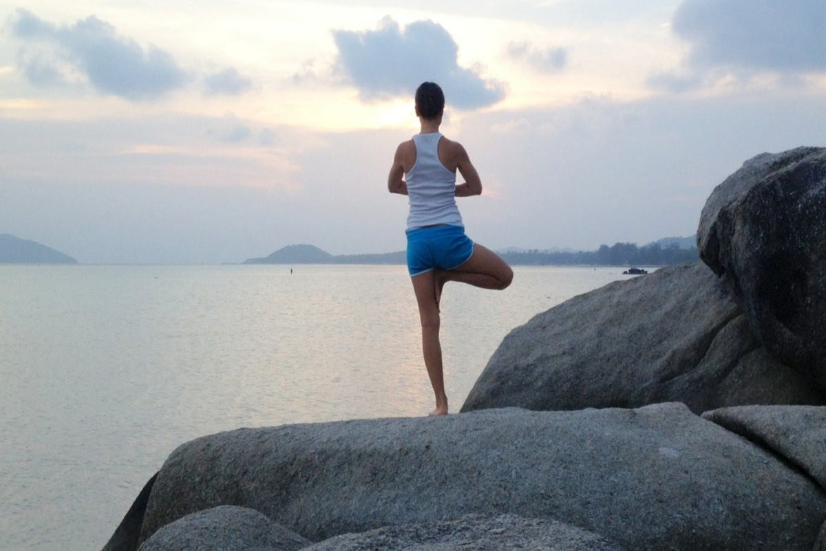 woman doing a yoga pose on a rock overlooking the ocean