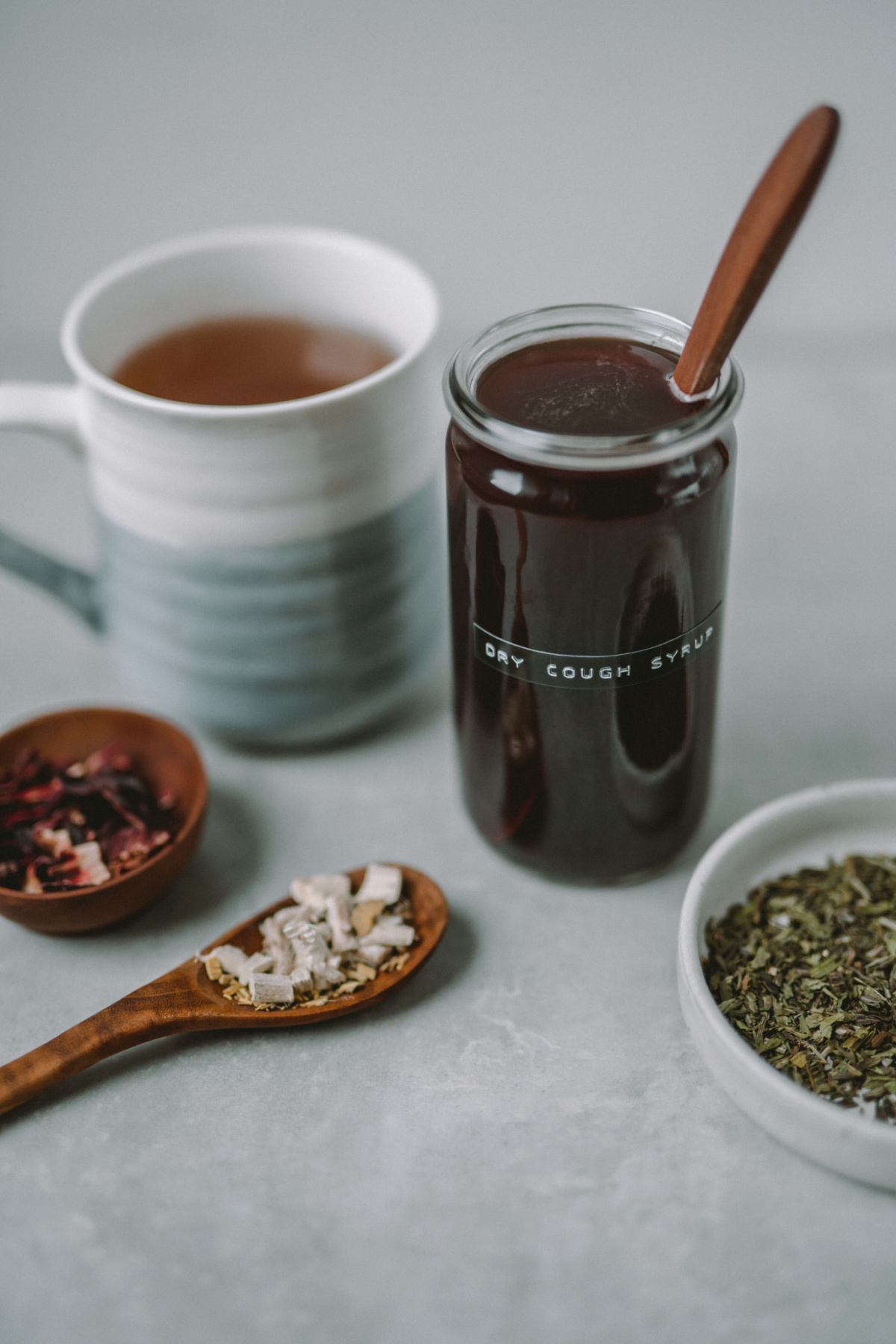 dry cough syrup recipe in a jar with dried herbs on table