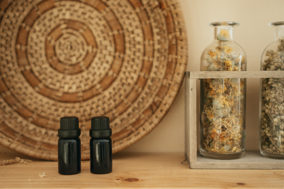 essential oil bottles on a shelf with a wicker basket and bottles of herbs