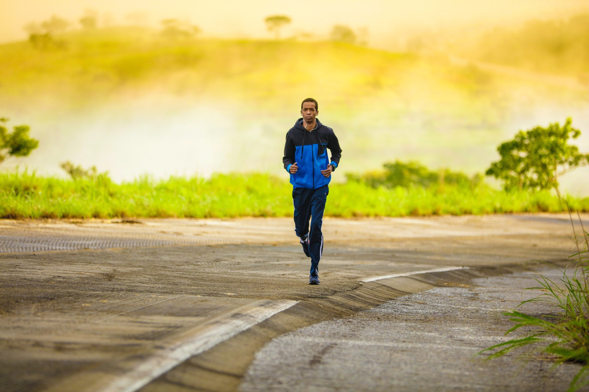 man jogging down a paved road