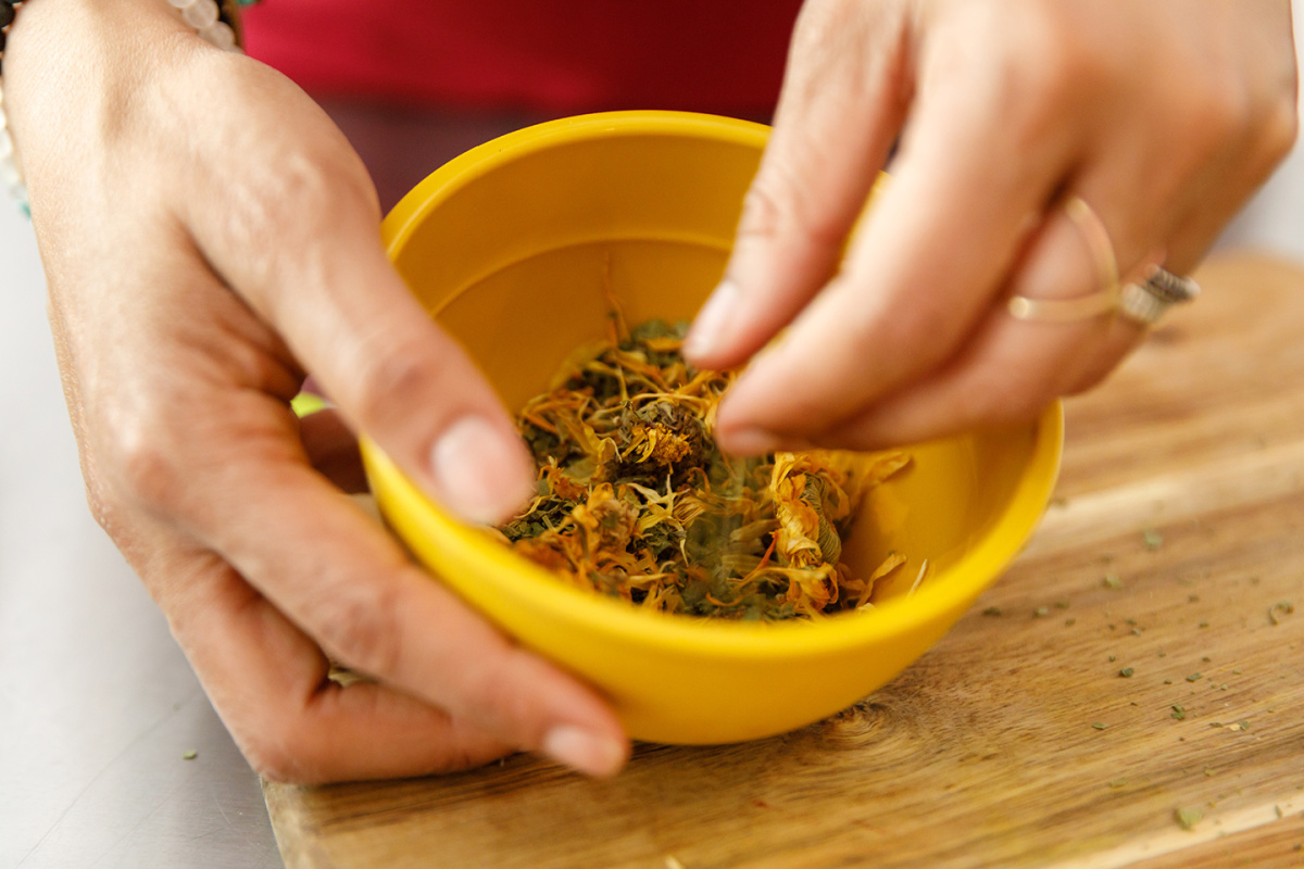 hands taking dried calendula flowers from a bowl