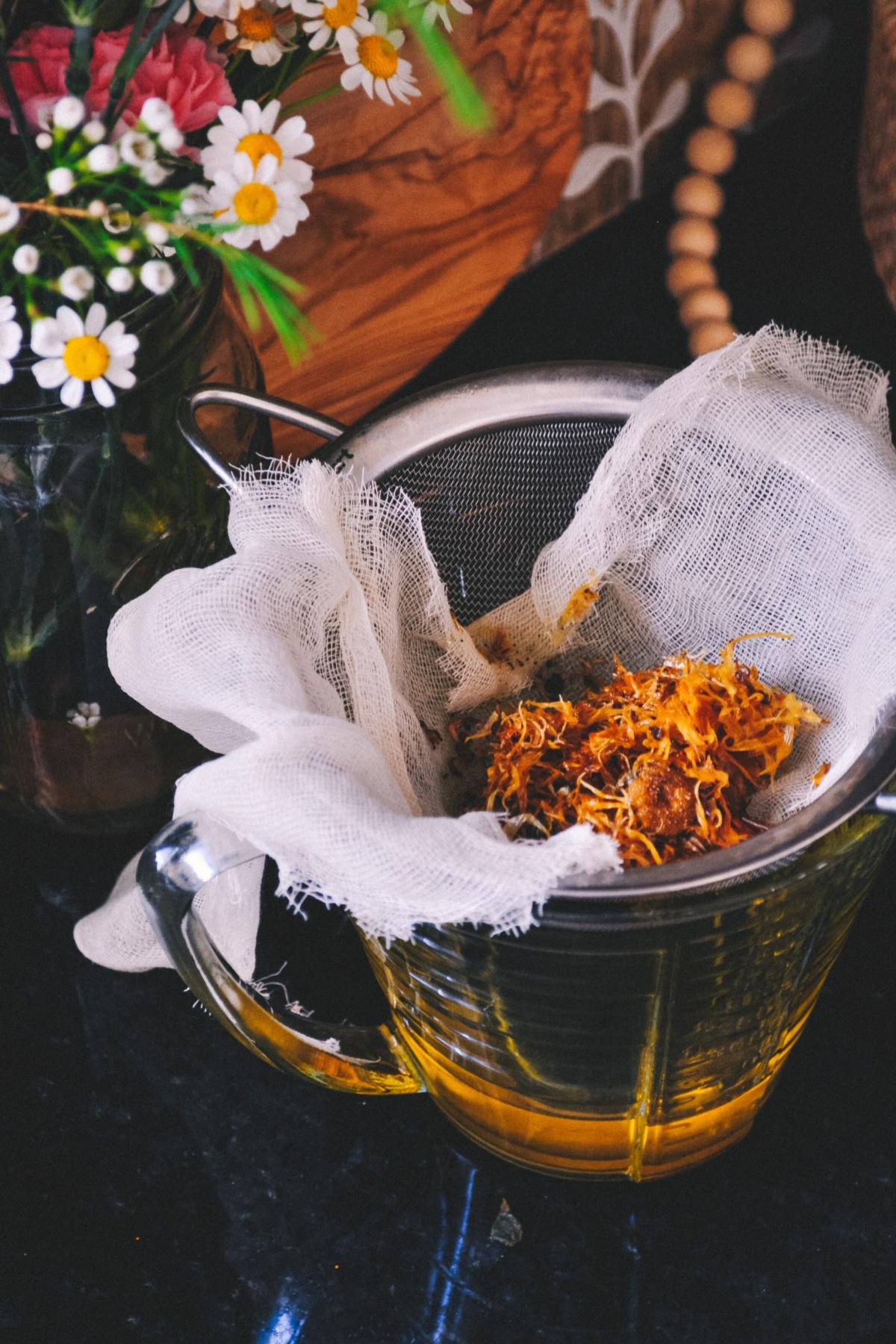 straining herbs through cheesecloth