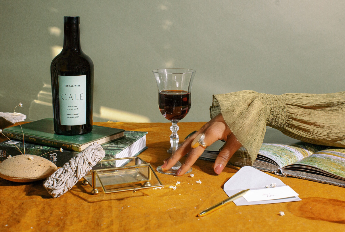 a table of books, wine glass, wine bottle