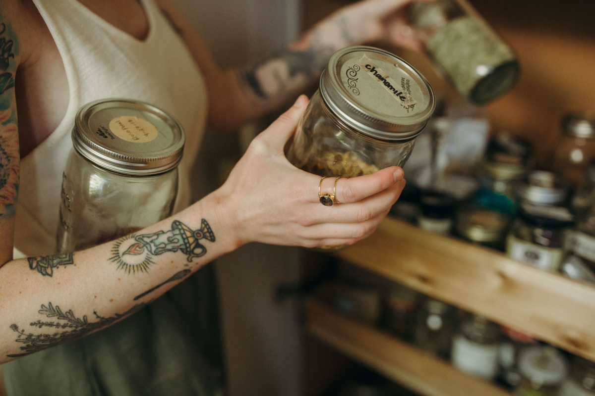 holding jars of dried herbs