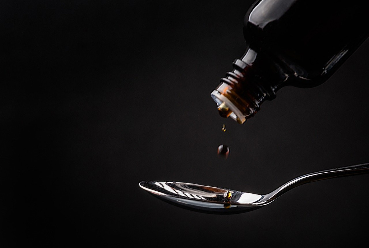 cough syrup dripping on a spoon