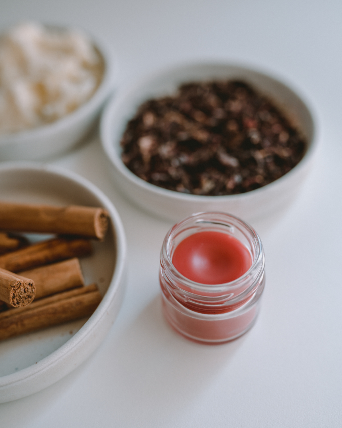 lip balm on a table with ingredients in the background