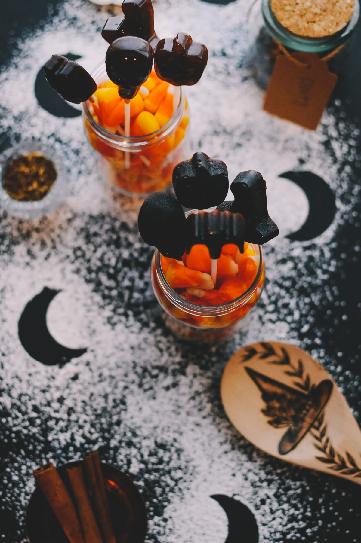 jars of candy corn with herbal lollipops and sugar sprinkled on the table